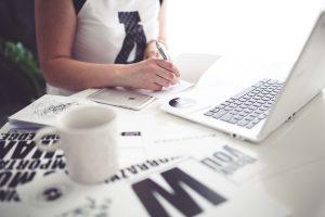 Person med bärbar dator och kaffekopp som arbetar online med en skrivarkurs.