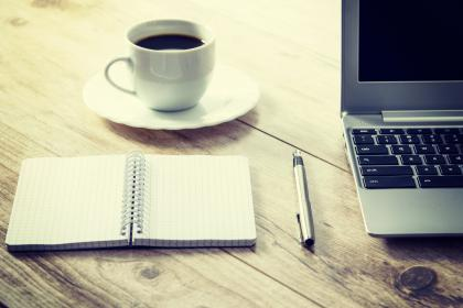 Skrivarkurser. På bilden syns en kaffekopp, anteckningsblock, penna och dator.