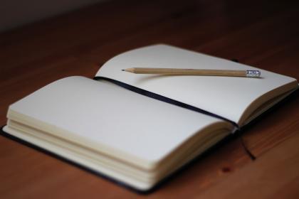 En bild på en uppslagen anteckningsbok och en penna illustrerar onlinekursen Skriv en roman på sex månader.